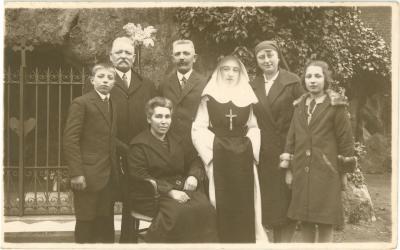 Familiefoto met kloosterzuster, 25 maart 1928