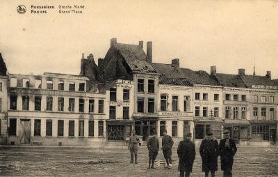 Enkele mannen en soldaten voor vernielde huizen op de Grote Markt