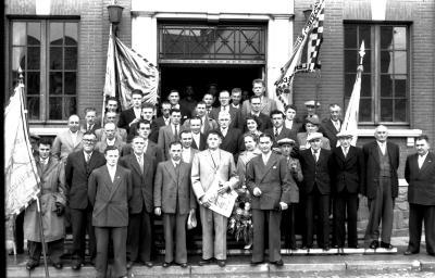 Kampioenviering vinkenzetters: groepsfoto aan gemeentehuis samen met burgemeester, Emelgem 18-08-1957